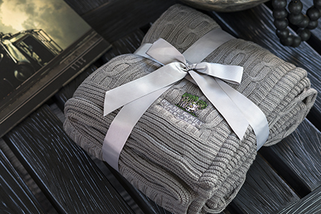 Gray Cable Knit Throw Blanket wrapped in a gray satin bow